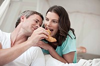 Germany, Hamburg, Couple in bedroom, woman biting into croissant