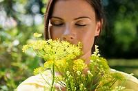 Germany, Hamburg, Woman in garden, smelling flower