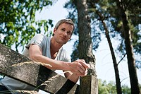 Germany, Hamburg, Man leaning against wooden fence, low angle view