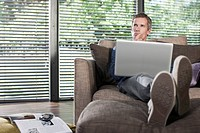 Germany, Hamburg, Man in living room using laptop