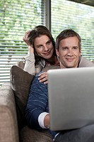 Germany, Hamburg, Couple in living room using laptop