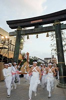 Rice bales being carried through a torii gate at Hadaka Matsuri Naked Festival, Hofu city, Yamaguchi Prefecture, Japan, Asia