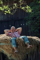 Germany, Bavaria, Senior man lying on haystack