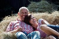 Germany, Bavaria, Couple lying on haystack