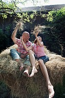 Germany, Bavaria, Couple sitting on haystack, fooling about, portrait