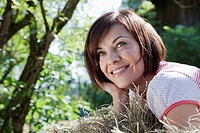 Germany, Bavaria, Woman lying in hay, smiling, portrait (thumbnail)