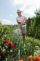 Germany, Bavaria, Senior man watering flowers, laughing, portrait