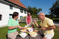 Germany, Bavaria, Two men at table in garden preparing food