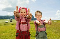 Italy, Seiseralm, Boy 6-7 and girl 8-9 in field, thumbs up, smiling, portrait, close-up (thumbnail)