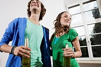 Germany, Berlin, Young couple holding beer bottles, laughing, portrait