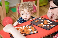 Germany, Berlin, Father and son 3_4 playing with toy tiles