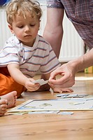 Germany, Berlin, Father helping son 3_4 to put puzzle together