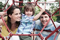 Germany, Berlin, Family at playground looking through climbing net, portrait, close_up