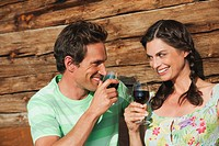 Italy, South Tyrol, Couple in front of log cabin holding wine glasses, smiling, portrait
