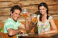 Italy, South Tyrol, Couple holding beer mugs, smiling, portrait