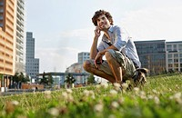 Germany, Berlin, Young man using mobile phone, smiling, portrait