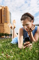Germany, Berlin, Young woman lying in meadow using mobile phone, portrait