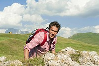 Italy, South Tyrol, Man standing by rock, smiling, portrait