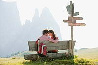 Italy, South Tyrol, Seiseralm, Couple sitting on bench, head to head