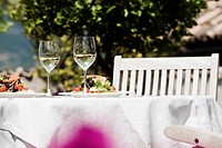 Italy, South Tyrol, Laid table, with mixed salad on plates and two glasses with white wine