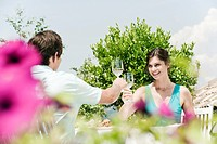 Italy, South Tyrol, Couple in restaurant toasting with white wine, smiling