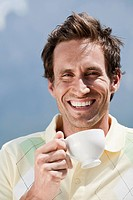 Italy, South Tyrol, Man holding cup of coffee, outdoors, laughing, portrait, close_up