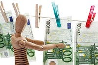 Wooden figurine, 100 Euro bank notes hanging on clothesline, close_up