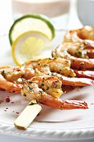 Skewered shrimps on plate, close_up
