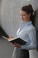 Germany, Cologne, Businesswoman in office holding personal organizer, side view, portrait