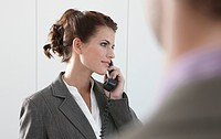 Germany, Cologne, Businesswoman using phone, looking away