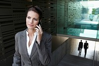 Germany, Cologne, Businesswoman on staircase using mobile phone, businessmen in background