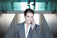 Germany, Cologne, Businesswoman using mobile phone, smiling