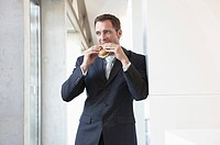 Germany, Cologne, Businessman eating sandwich