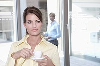 Germany, Cologne, Businesswoman in office taking a coffe break, business man in background