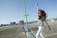 Germany, Berlin, Young woman dancing in empty parking lot, smiling