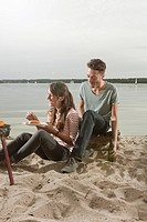 Germany, Berlin, Lake Wannsee, Young couple having a barbecue