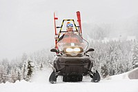 Italy, South Tyrol, Man driving snowmobile