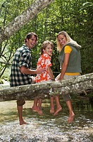 Austria, Salzburger Land, Family sitting on tree trunk, smiling