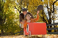 Austria, Salzburger Land, Man pushing soapbox car, boy 12_13 waving cap