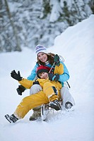 Germany, Bavaria, Mother and son 8_9 sledding downhill, laughing