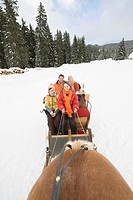 Italy, South Tyrol, Seiseralm, Family sitting in sleigh