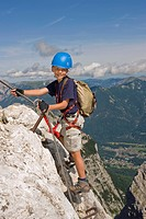 Germany, Garmisch_Partenkirchen, Alpspitz, Boy 10_11 climbing rock face on ladder, smiling, portrait