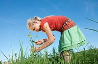 Germany, Bavaria, Girl 10_11 in meadow, examining flowers through magnifying glass