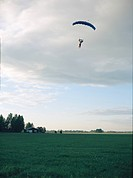 Parachute jumper in the sky over a field