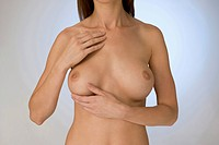 Nude woman touching her breast