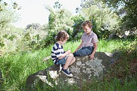 Two boys sitting on a rock