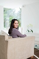 Young woman sitting on sofa