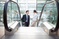 Germany, Bavaria, Munich, Airport, Businesspeople standing on escalator