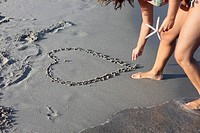 Italy, Sardinia, Person drawing heart in sand