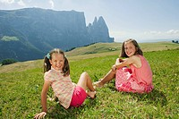 Italy, South Tyrol, Seiseralm,Two girls 6_7 10_11 sitting in meadow